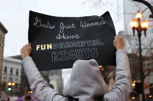 """A protester with a """"Girls Just Wanna Have Fundamental Rights"""" sign Photo by lucia on Unsplash."""