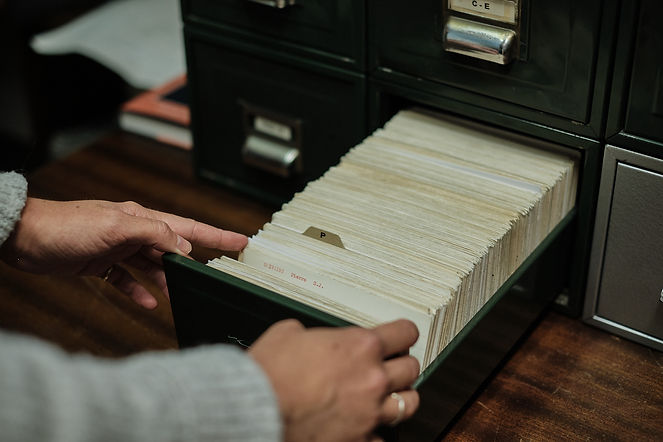 Hands at an open drawer with lots of small white cards