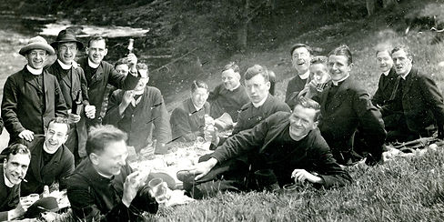 Black and white photograph showing group of young men wearing priest collars having picnic