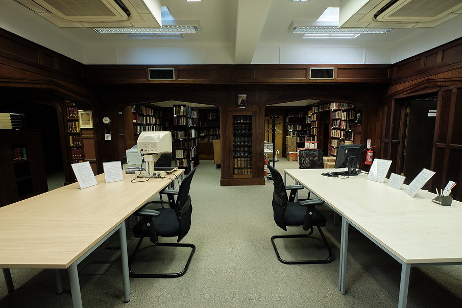 Photo of a space with big empty expect for some notices tables. In background library shelves.