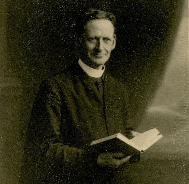 Photograph of a young man with clerical collar holding an open book looking at viewer