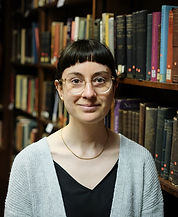 Profile photo of white woman smiling at camera with books in background
