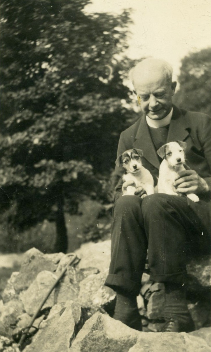 Black and white photograph of an older white man in clerical dress sitting on a rock with a tree in the background, holding two puppies
