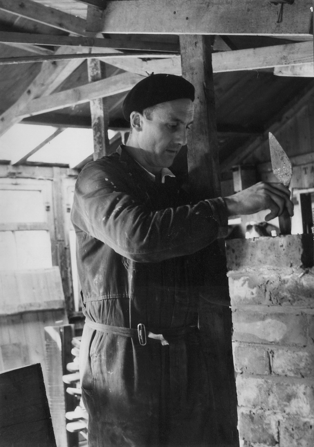 White male wearing a beret and overalls with a trowel in his hand held over a brick wall