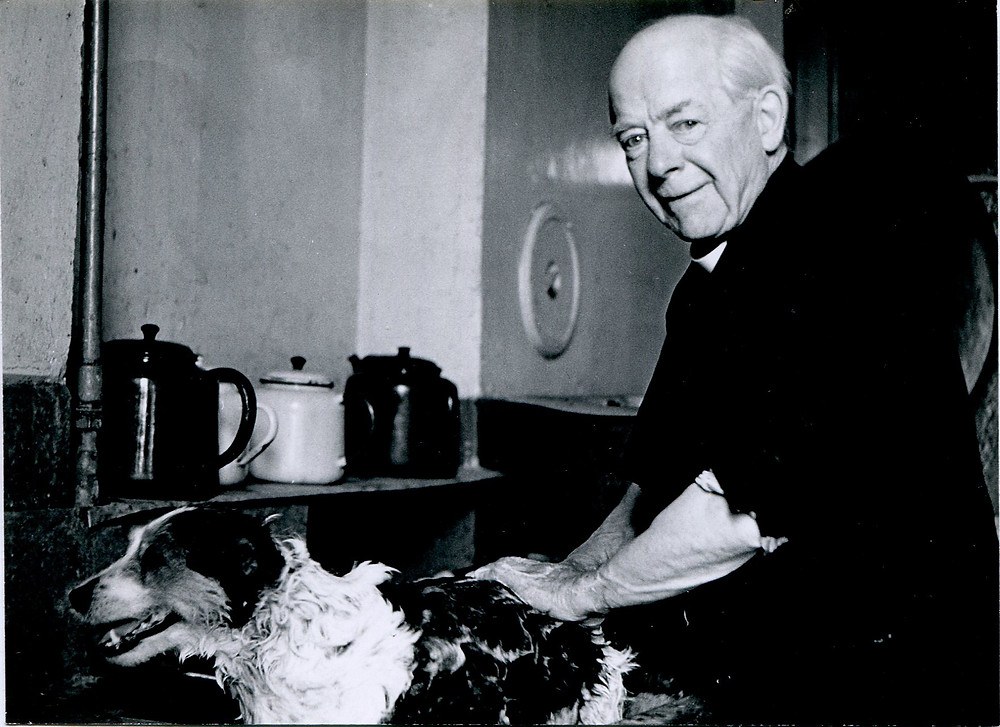 Black and white photograph of an older white man in clerical dress washing a dog in the sink