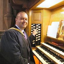 Darren Hogg, accompanist, seated at an organ
