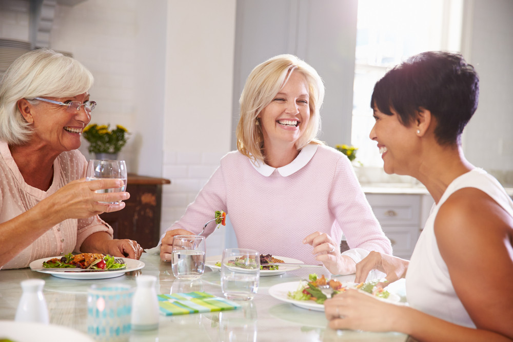 implant-supported-dentures-mature-woman-women-dentist-cosmetic-dentistry-eating-happy-group