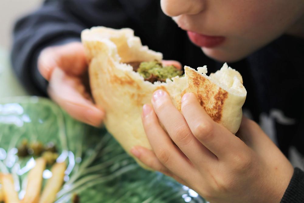 ילד אוכל פלאפל בפיתה