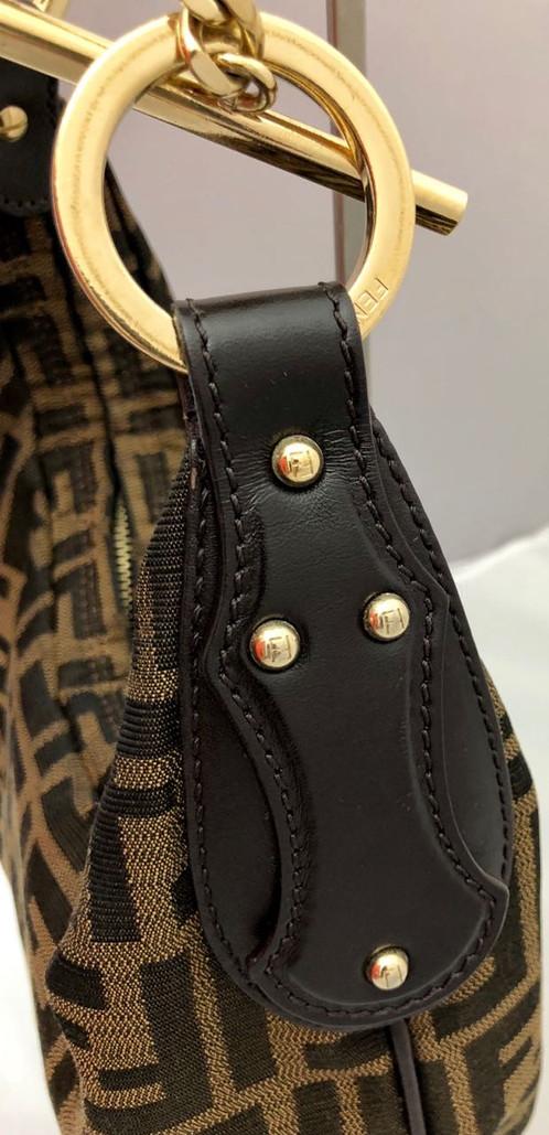 Bolsa Fendi confeccionada em tecido marrom com estampa do monograma em  preto. A peça possui detalhes em couro marrom presentes no entorno do zíper  e nas ... 5d88f2761a6