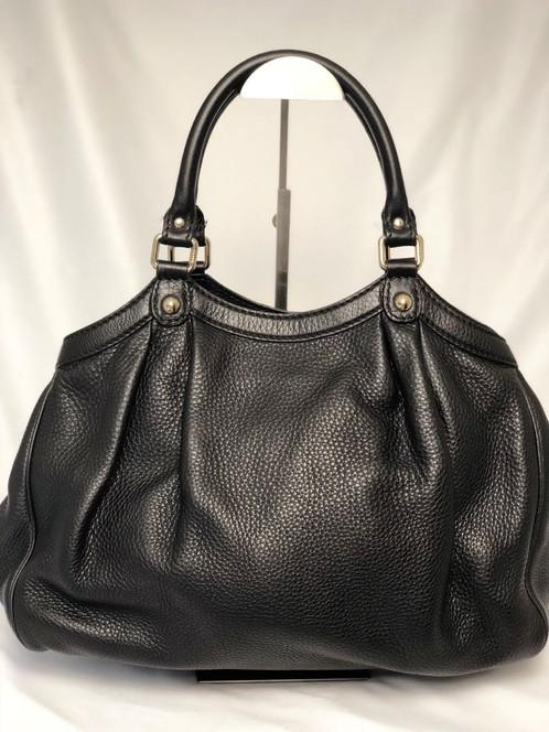 ce1f4be87 Bolsa Gucci Sukey Preta confeccionado em couro com estampa GG Canvas.  Modelo em tamanho grande, com alça dupla de ombro, tag da marca em couro,  ...