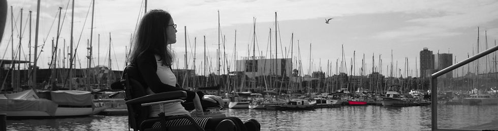 Netta Ganor sits in a wheelchair and looks at the marina in Barcelona