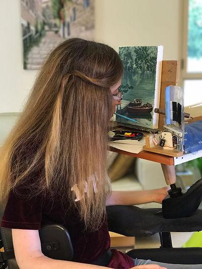 נטע גנור חותמת את שמה על ציור עם מכחול בפה