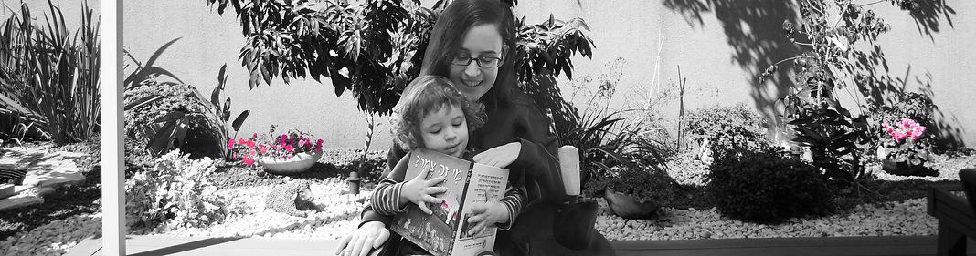 נטע גנור יושבת בכסא גלגלים עם בנה על ברכיה ומקריאה לו את ספר הילדים הראשון שלה