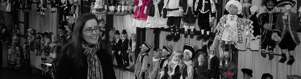 נטע גנור יושבת בכסא גלגלים בחנות בובות ומסתכלת על הבובות בחיוך