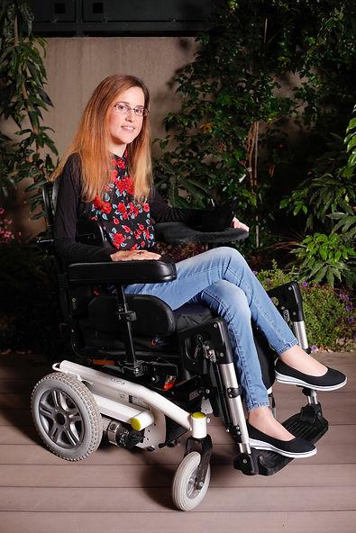 נטע גנור יושבת בכסא גלגלים ומחייכת למצלמה