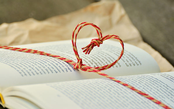 open book with bookmark knotted into a heart shape