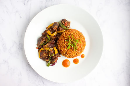 Nigerian Jollof Rice and Asun (Spicy Goat Meat) served with a Bell Pepper Sauce