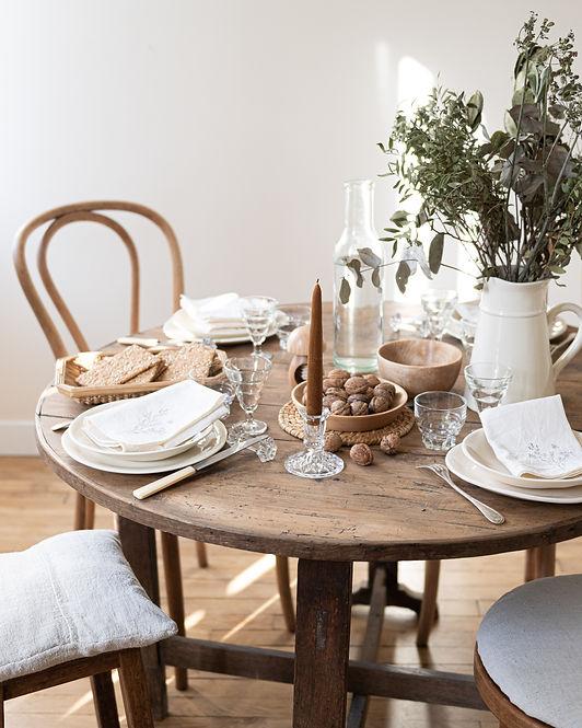 Une jolie table avec de la vaisselle en faïence ivoire artisanale et fabriquée en France, des couverts et des verres anciens chinés en France