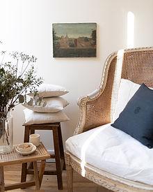 joli salon avec huile sur toile et coussin en chanvre anciens, fauteuils Louis XVI canné et vaisselle artisanale en faïence ivoire fabriquée en France