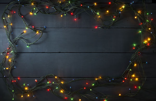 Glowing Christmas tree garland in the form of a frame on a blue wooden background.jpg