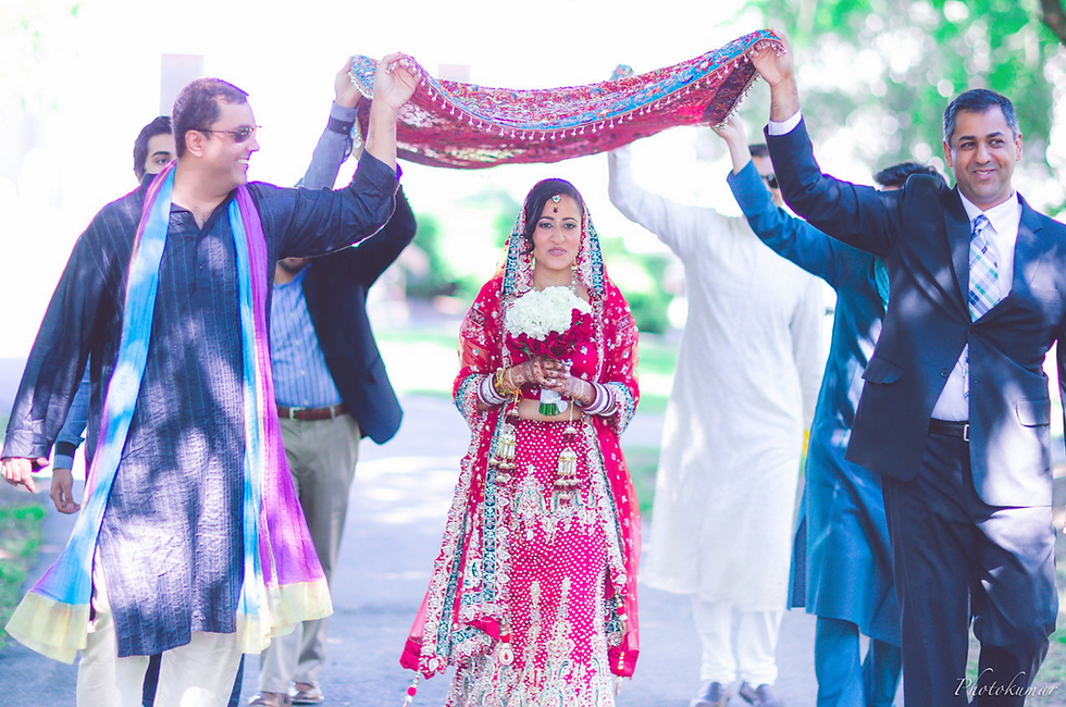 Beautiful Indian bride entering the wedding ceremony with her loved ones.