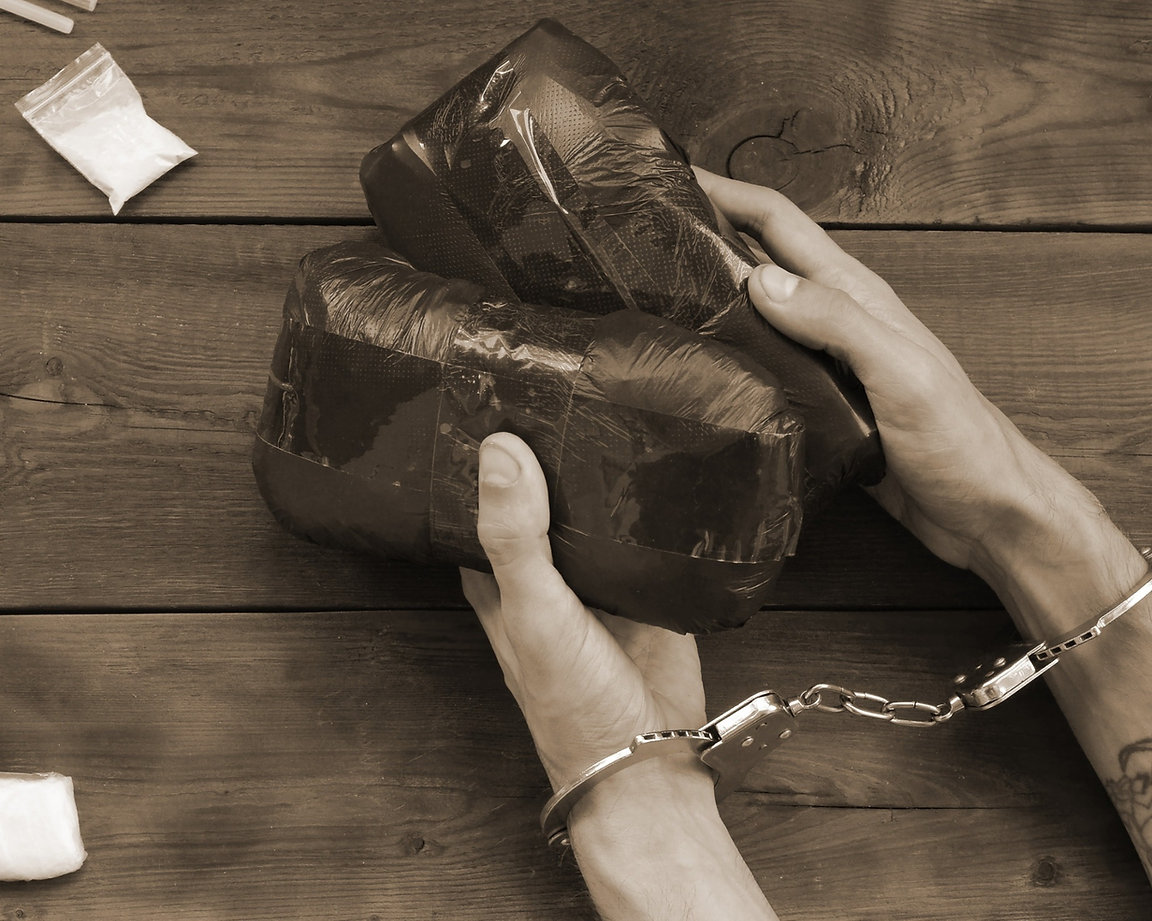 a guy handcuffed with bags of drugs in his hands.jpg
