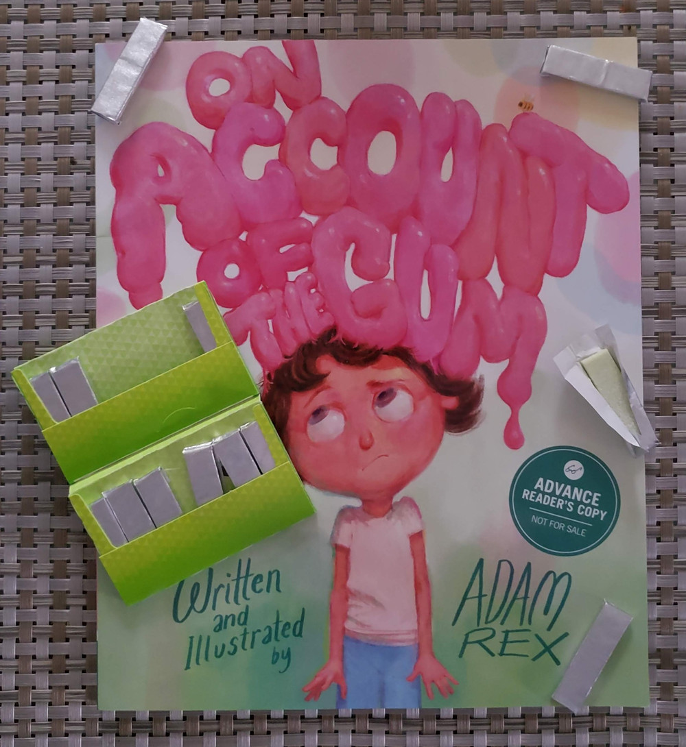 The book On Account of the Gum by Adam Rex is laying on a patterned mat with a pack and pieces of gum posed around it.
