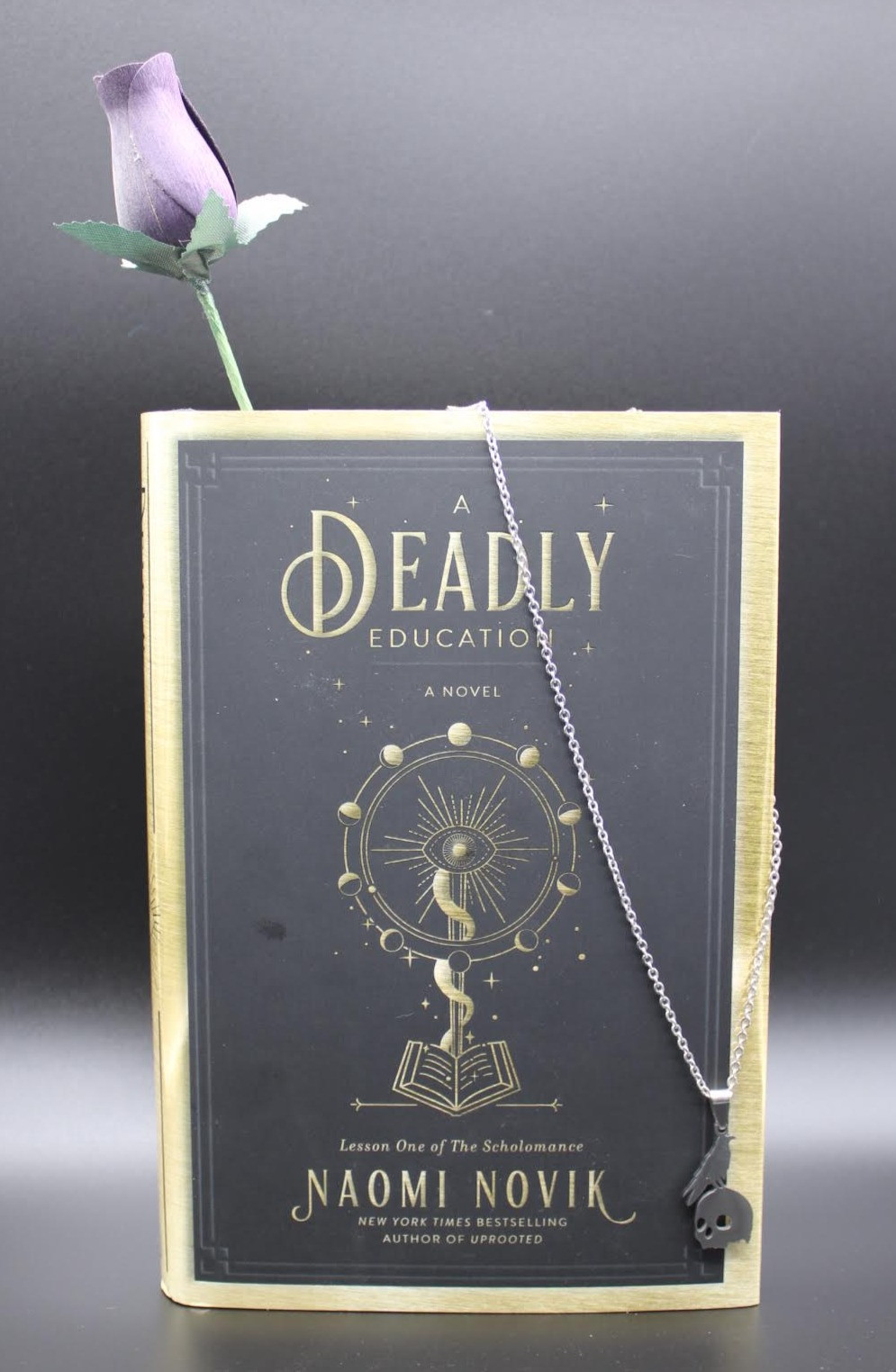 The book A Deadly Education by Naomi Novik stands in front of black backdrop with a purple rose sticking out of the top of the book and a silver chain drooped on the right side.