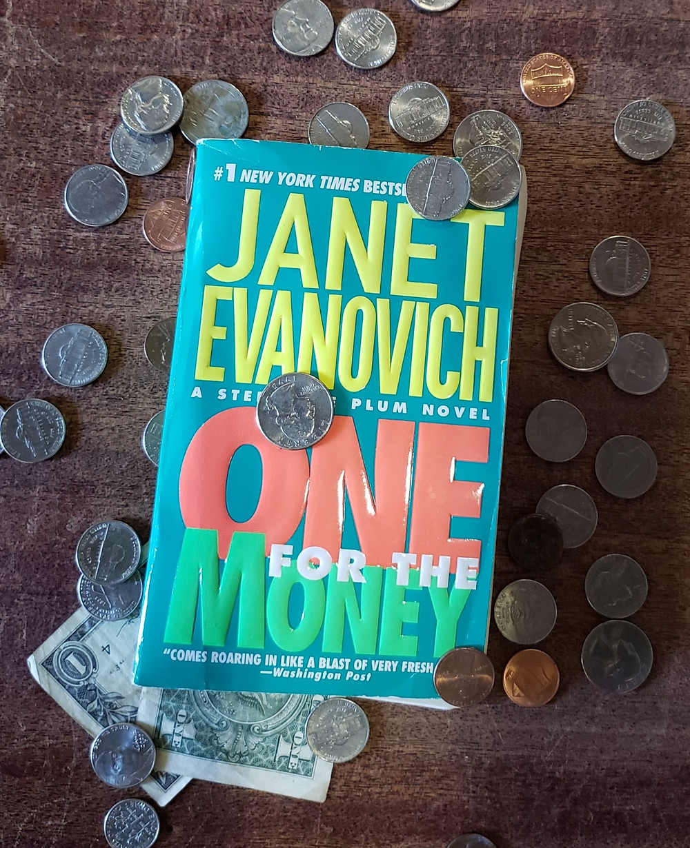 The book One for the Money by Janet Evanovich is laying on a wooden background surrounded by coins. A one dollar bill is tucked under the book's lower left corner.