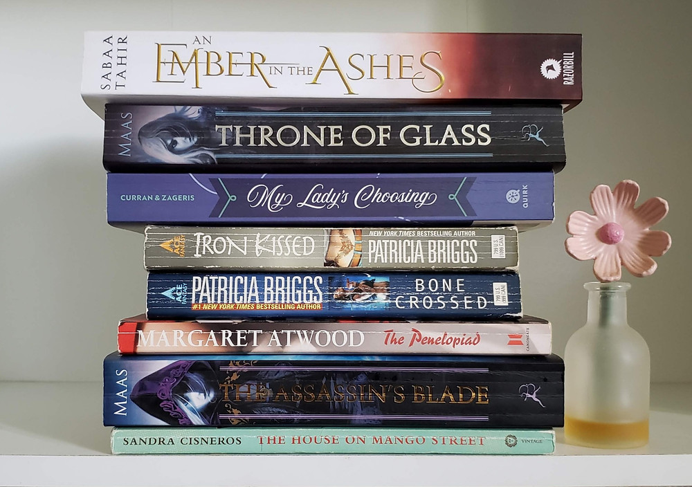 Stack of books with a decorative flower to the righthand side. From top to bottom the books are An Ember in the Ashes by Sabaa Tahir, Throne of Glass by Sarah J. Maas, My Lady's Choosing by Kitty Curran and Larissa Zageris, Iron Kissed by Patricia Briggs, Bone Crossed by Patricia Briggs, The Penelopiad by Margaret Atwood, The Assassin's Blade by Sarah J. Maas, The House on Mango Street by Sandra Cisneros.