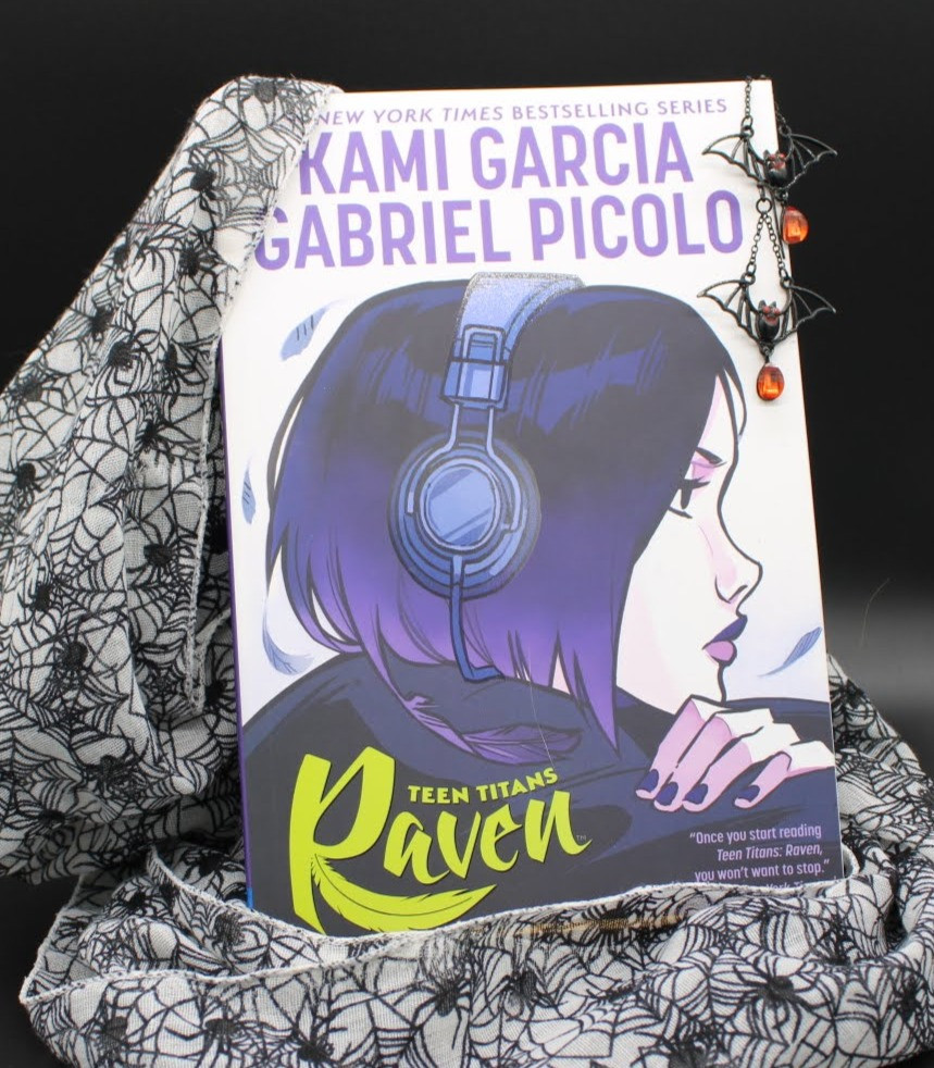 The book Teen Titans Raven by Kami Garcia and Gabriel Picolo has black and orange bat earrings hanging from the top right corner, a spider patterned scarf draped around, and posed in front of a black background.
