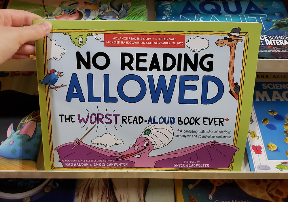 The book No Reading Allowed by Raj Haldar, Chris Carpenter, and Bryce Gladfelter is posed in front of some face-out bookcases full of other children's books and being held in place by a hand in the upper left corner.