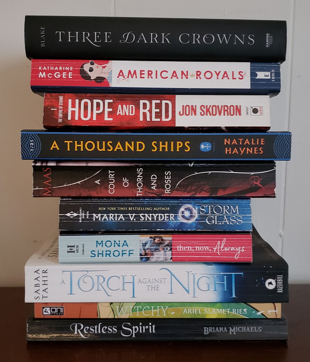 A stack of books with their spines facing forward. From top to bottom they are Three Dark Crowns by Kendare Blake, American Royals by Katharine McGee, Hope and Red by Jon Skovron, A Thousand Ships by Natalie Haynes, A Court of Thorns and Roses by Sarah J. Maas, Storm Glass by Maria V. Snyder, Then Now Always by Mona Shroff, A Torch Against the Night by Sabaa Tahir, Witchy by Ariel Slamet Ries, and Restless Spirit by Briana Michaels.