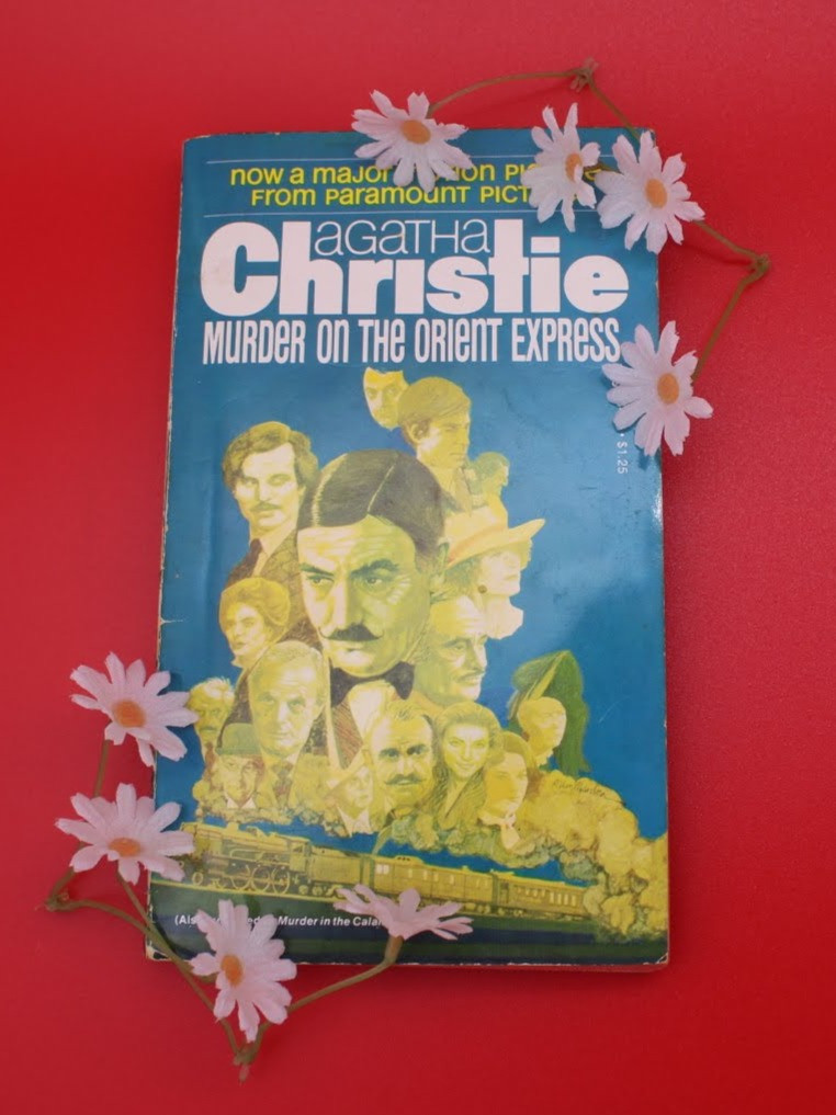 The book Murder on the Orient Express by Agatha Christie is in front of a red background with small daisies spread all around.