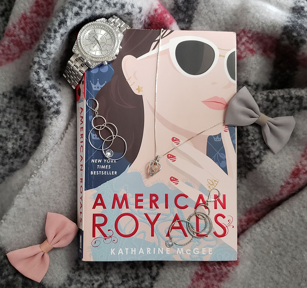 The book American Royals by Katharine McGee is laying on a pink and gray scarf. Jewelry decorates the book. There is a silver watch on the upper left corner, two multi-circle silver earrings, pink and gray bows, and a silver necklace with a pink pearl in a little cage as the pendent.