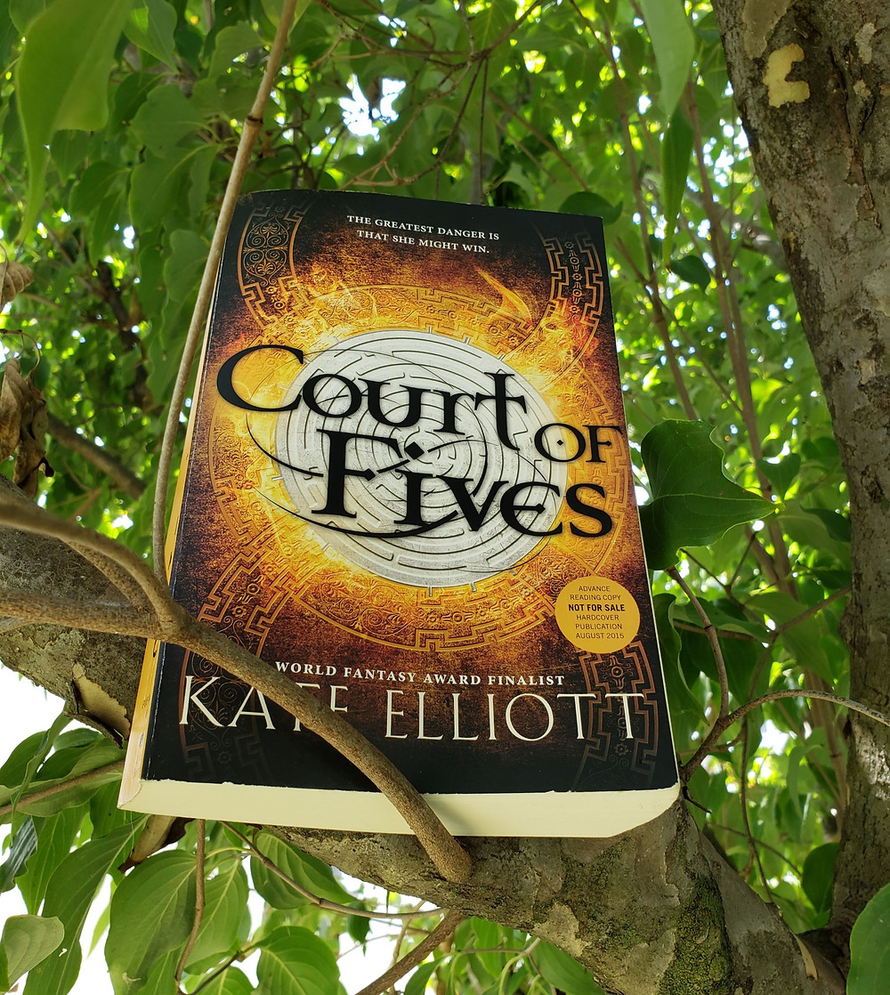 The book Court of Fives by Kate Elliott posed in a tree, sitting on a branch, and surrounded by green leaves.