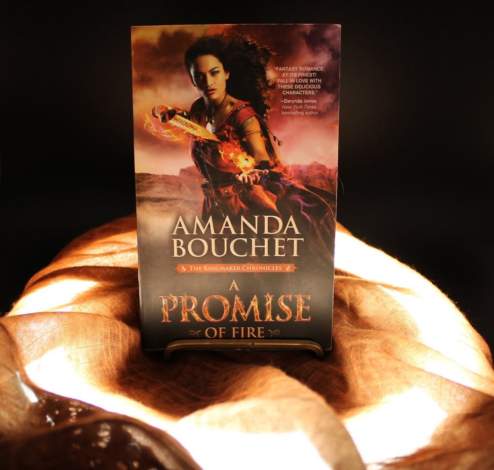 The book A Promise of Fire by Amanda Bouchet is positioned in a circle of light draped with a cloth.