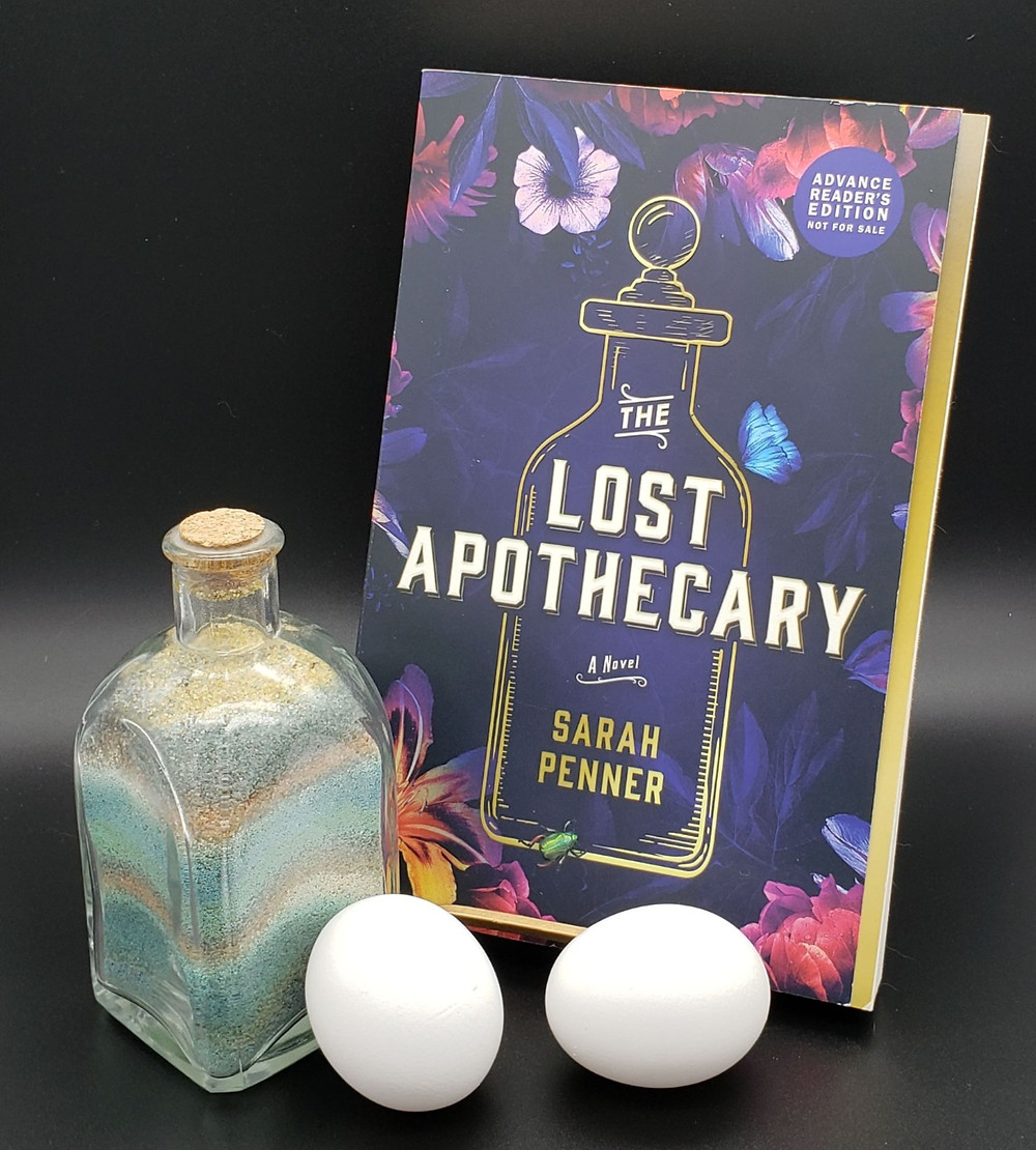 The book The Lost Apothecary by Sarah Penner is sitting in a bookstand with a jar of colored sand to its left and two white eggs in front.