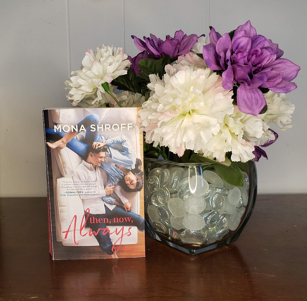 The book Then, Now, Always by Mona Shroff is posed to the left of a bouquet of purple and white flowers in a glass vase.
