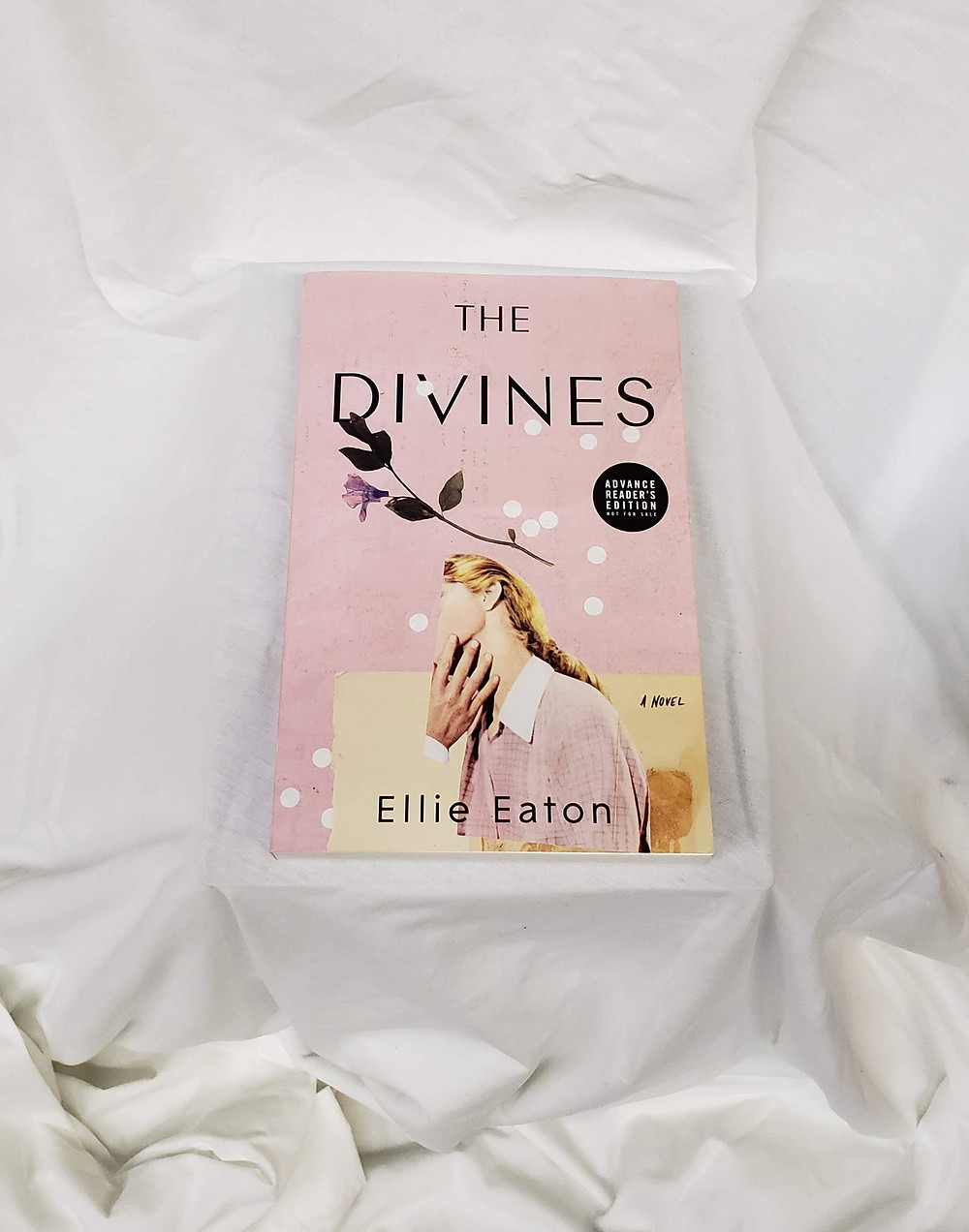The book The Divines by Ellie Eaton is posed, front cover up, on a white sheet draped around the book.