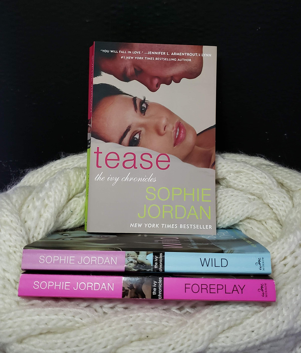 The book Tease by Sophie Jordan is propped up on the other two books in the series, Foreplay and Wild. They are all nestled in a white knitted cloth with a back background.