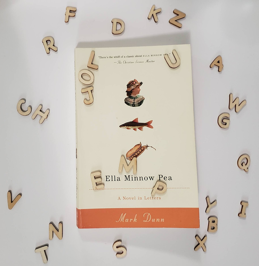 The book Ella Minnow Pea by Mark Dunn laying on a white background surrounded by wooden letters.