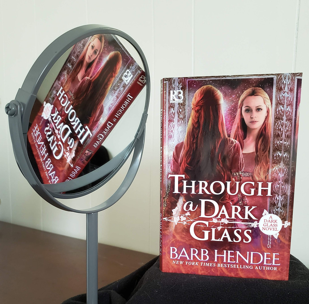 The book Through a Dark Glass by Barb Hendee is propped up on a dark cloth and positioned so it's reflection appears in a mirror to the left in the image.