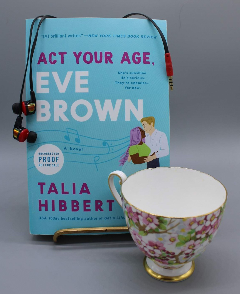 The book Act Your Age, Eve Brown by Talia Hibbert is sitting upright in a gold bookstand in front of a grey background. There is a pink flower decorated teacup in front of the book's lower right corner and a pair of red and black corded earbuds draped across the top of the book.