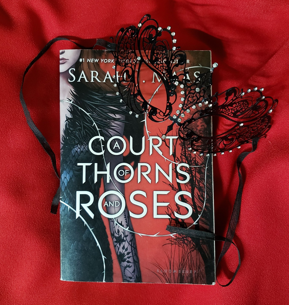 Image of front cover of A Court of Thorns and Roses by Sarah J. Maas. The book rests on a red cloth similar to the red on the cover with a black lace eye mask draped over the top right corner.