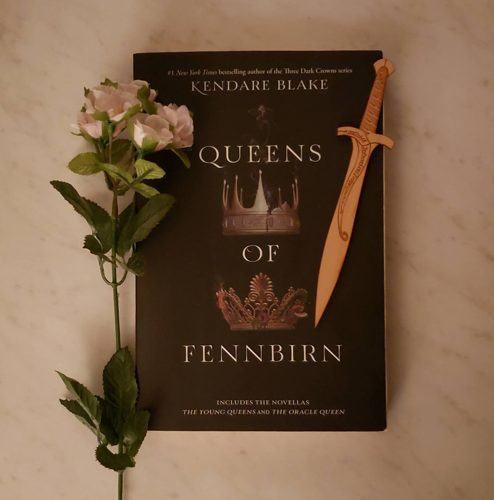 The book Queens of Fennbirn by Kendare Blake is laying on a white marble surface with a stem of pink flowers along the left of the book and a wooden sword on the right.
