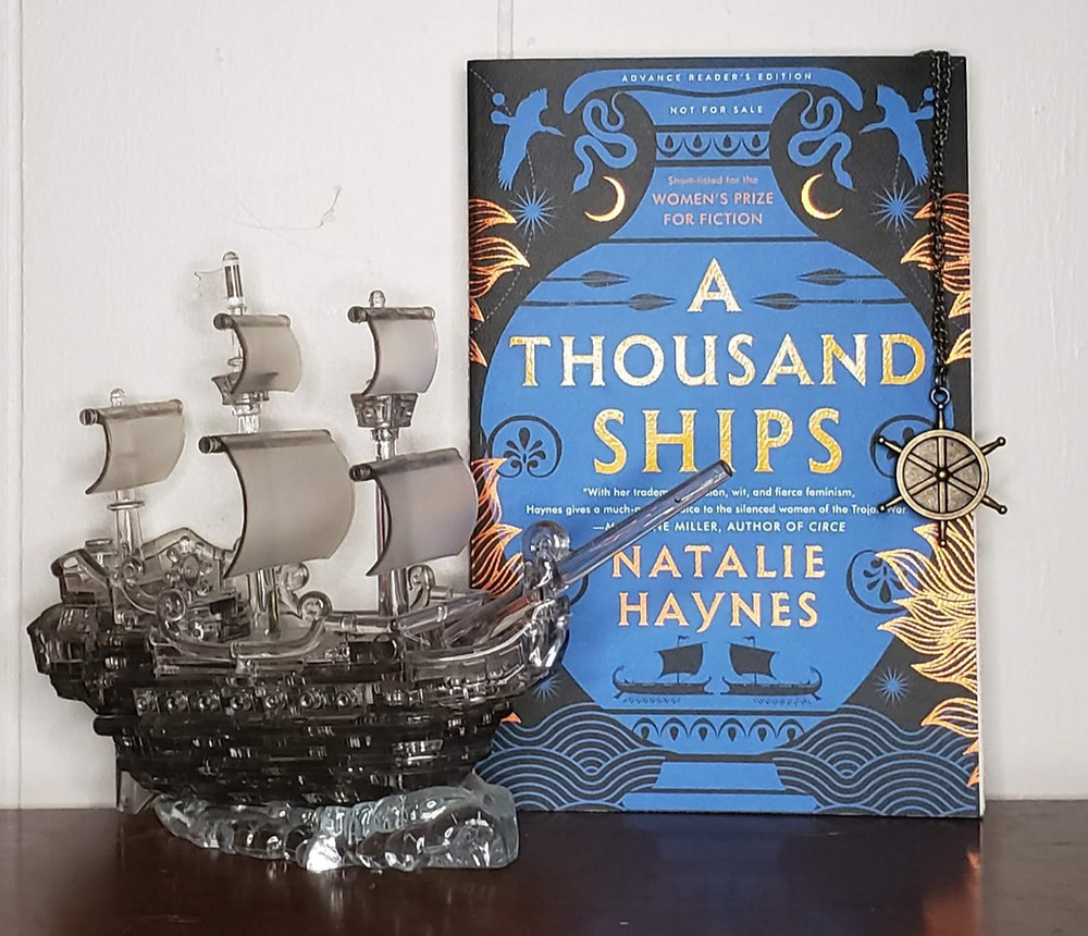 The book A Thousand Ships by Natalie Haynes is posed to the right of a gray crystal pirate ship and from the top of the book's right corner hangs a brass ship wheel on a chain.
