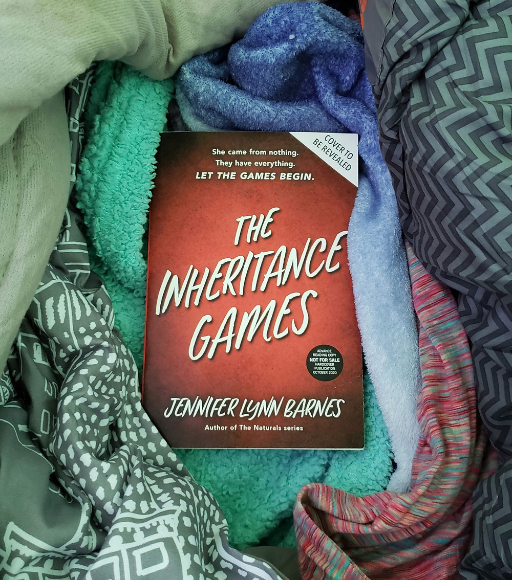 The book The Inheritance Games by Jennifer Lynn Barnes is laying in some crumpled blankets.