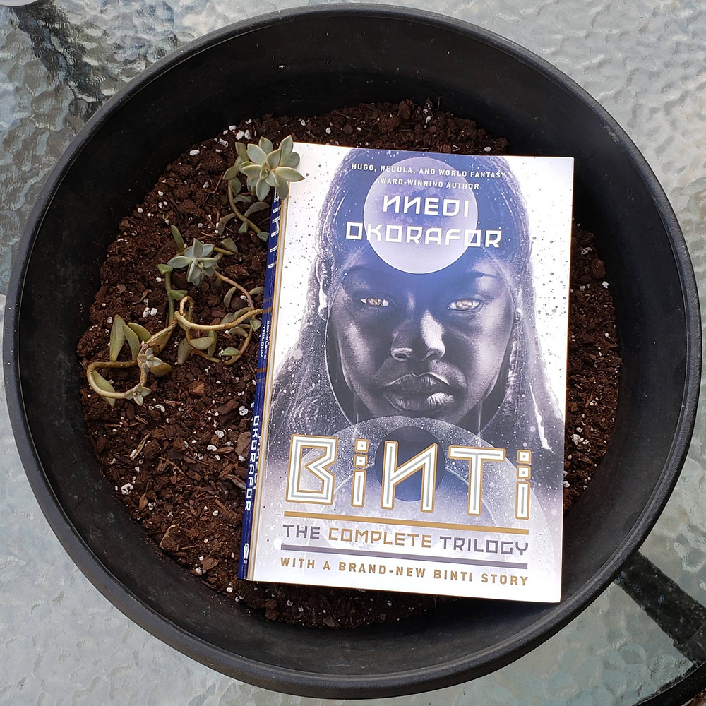 The book Binti by Nnedi Okorafor is set in a large plant pot. From a high view looking down you see the book on some soil and a light green succulent plant growing around and slightly overlapping the book on the left.