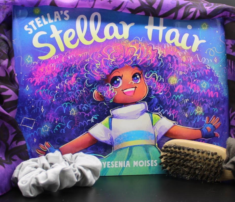 The book Stella's Stellar Hair by Yesenia Moises is standing upright with a purple scarf draped across the top. A wooden hairbrush and scrunchies sit in front of the book.